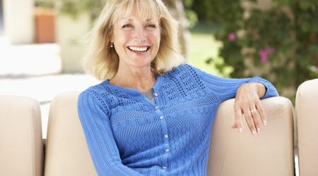Senior Woman Relaxing On Sofa At Home Wearing Blue Cardigan Smiling At Camera